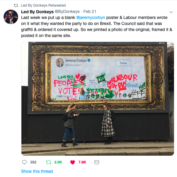 Image of a Twitter post showing graffiti'd billboard