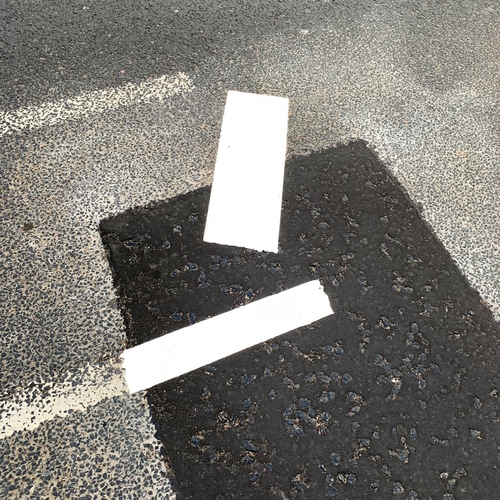 A photograph of repainted white street markings on a tarmac surface.