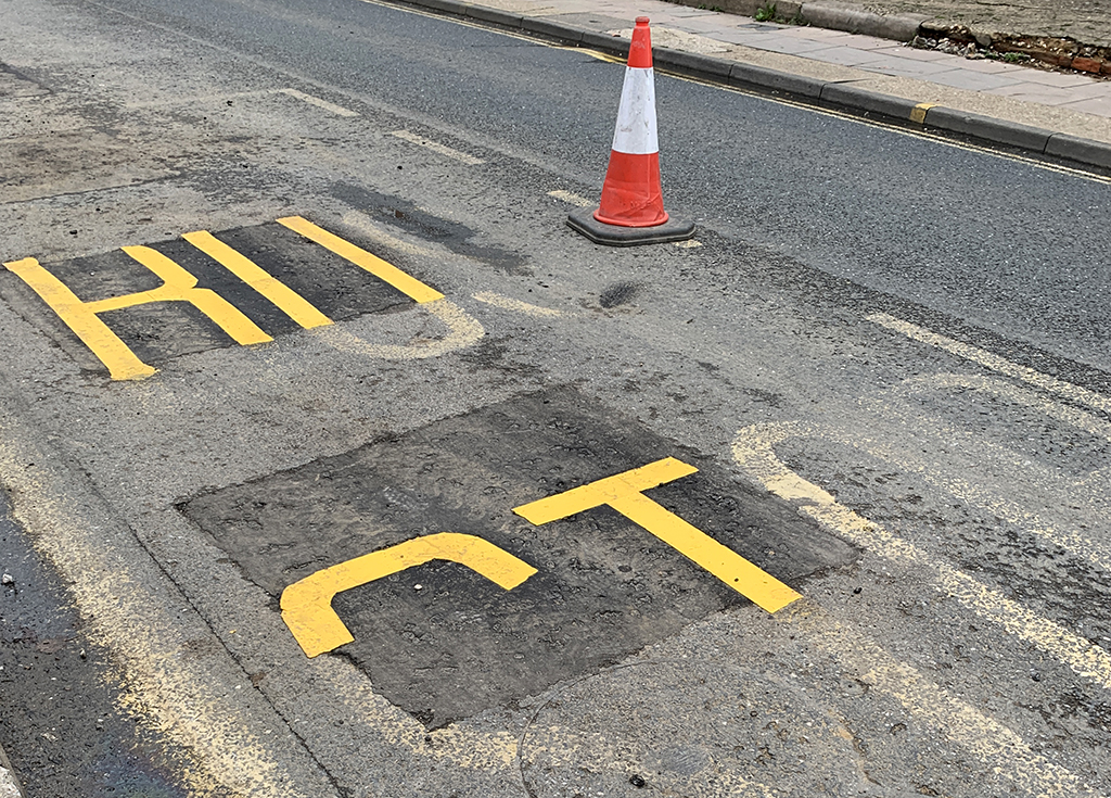 A photograph of the words Bus Stop partially painted on a street after road works have taken place with a road cone.
