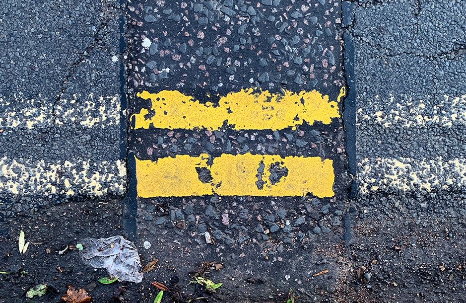 A photograph looking down at the gutter of a street focusing on repainted double yellow 'no parking' lines that look like an equals sign.