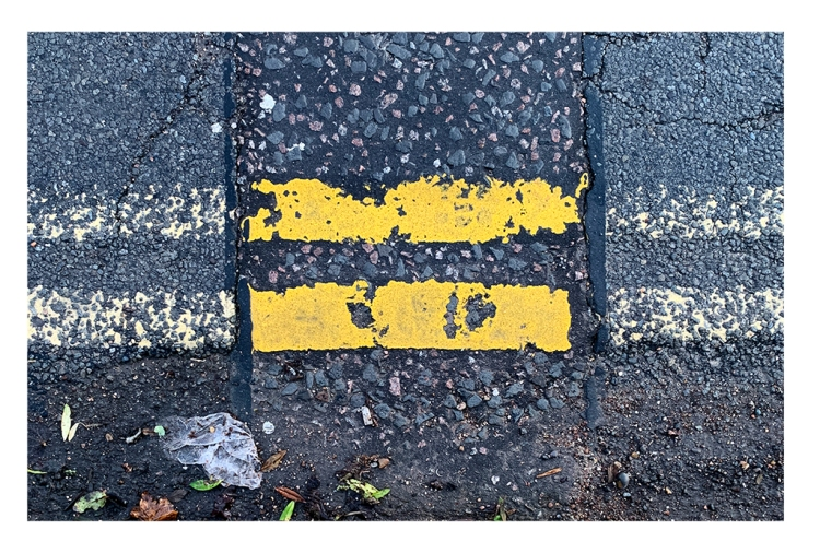 A photograph of repainted double yellow lines painted on the road