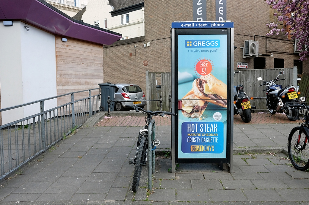 A photograph of a telephone box with an advert for Greggs applied to its door. This telephone box sits in a pedestrianised area, with bicycles and motorbikes parked around it, and a parked car can be seen in the distance between two buildings