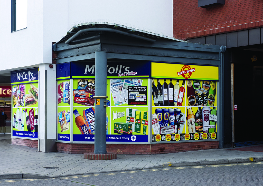 A photograph of a convenience store corner shop window, covered from edge to edge in a vinyl print of products the shop sells, including wine bottles, biscuits, confectionary and tobacco products.